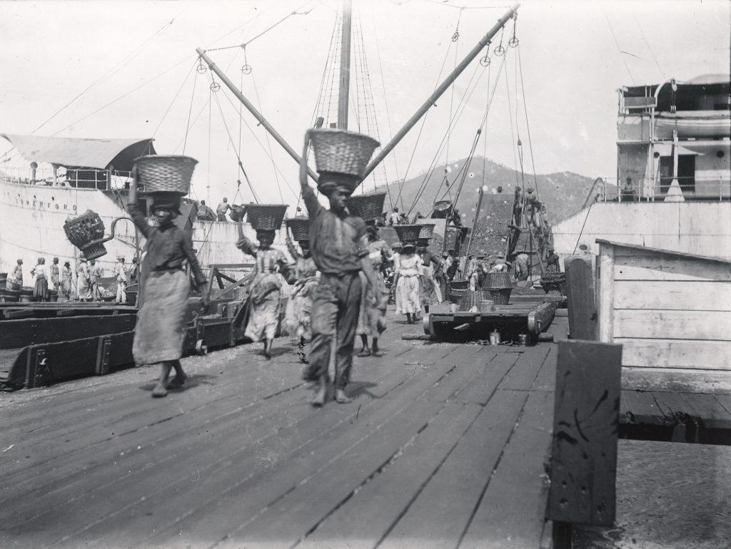 Kvindelige og mandlige daglejere bærer kul ombord på dampskibe i St. Thomas havn.